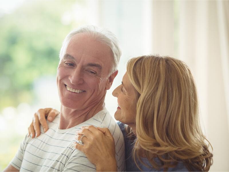 Older Couple Embracing After Dental Implant Procedure
